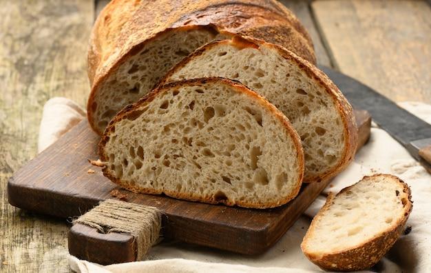 Pieczony okrągły chleb z białej pszennej deski na drewnianej desce, bochenek pokrojony na kawałki, z bliska