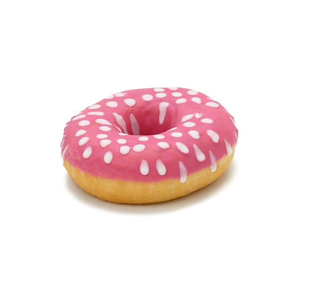 Pieczony okrągły pączek z różowym lukrem i białymi kropkami na białym tle, z bliska