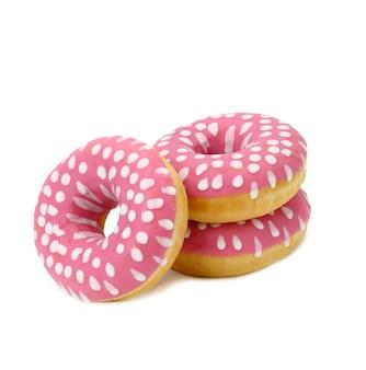 Pieczony okrągły pączek z różowym lukrem i białymi kropkami na białym tle