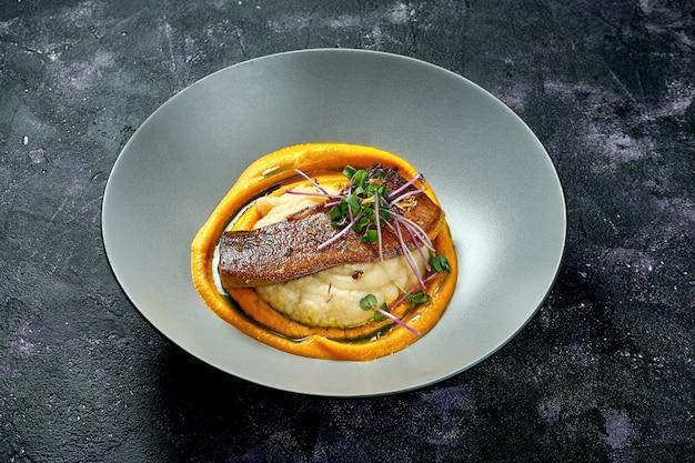 Pieczony ozór wołowy z puree ziemniaczanym i marchewką w szarej misce na czarnej powierzchni. ścieśniać. selektywna ostrość