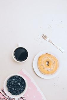 Pieczony pączek; filiżanka kawy; serwetka; widelec i jagody na białym tle