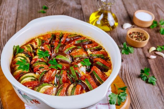 Pieczony ratatouille warzywny z mozzarellą na białej patelni piekarnika.