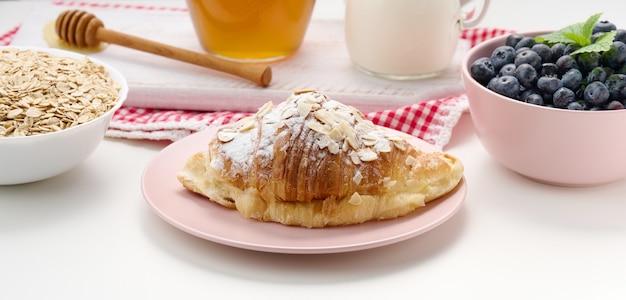 Pieczony rogalik posypany cukrem pudrem, jagodami i płatkami owsianymi w ceramicznym talerzu na białym stole, śniadanie