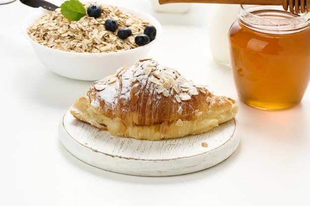 Pieczony rogalik posypany cukrem pudrem, płatki owsiane w ceramicznym talerzu na białym stole, śniadanie