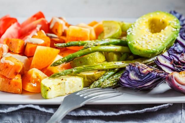 Pieczony słodki ziemniak, szparagi, kapusta, cukinia ze świeżymi pomidorami i awokado na szarym talerzu.