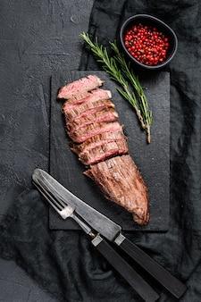 Pieczony średnio rzadki stek wołowy w plastrach. czarne tło. widok z góry