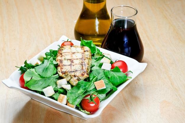 Pieczony stek jagnięcy z czarnym pieprzem z sałatkami i frytkami na niebieskim okrągłym talerzu. drewniane tekstury tła.