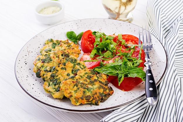 Pieczony stek posiekany filet z kurczaka ze szpinakiem i przystawką z sałatką z pomidorów. kuchnia europejska. żywność dietetyczna.