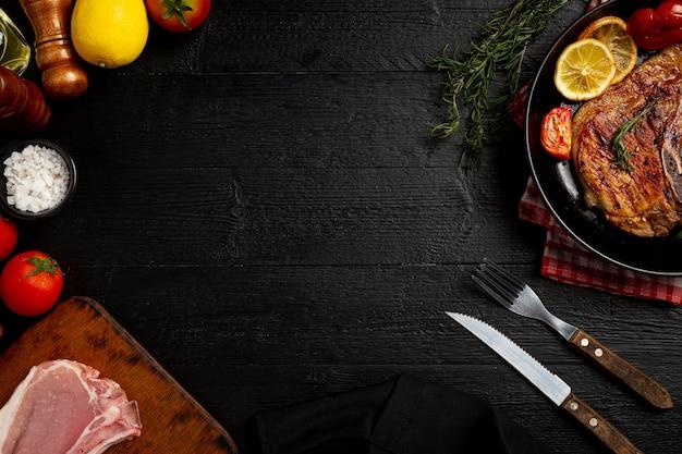 Pieczony stek wieprzowy na ciemnej drewnianej powierzchni.