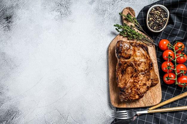 Pieczony stek wieprzowy na desce do krojenia. mięso ekologiczne. szare tło.