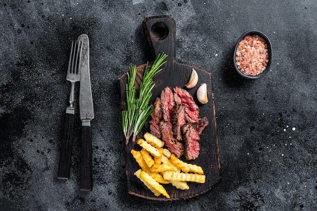 Pieczony stek wołowy z maczetą w plasterkach na drewnianej desce z frytkami. czarne tło. widok z góry.