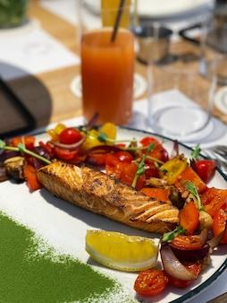 Pieczony stek z łososia z dodatkami warzywnymi na talerzu. zdrowy posiłek