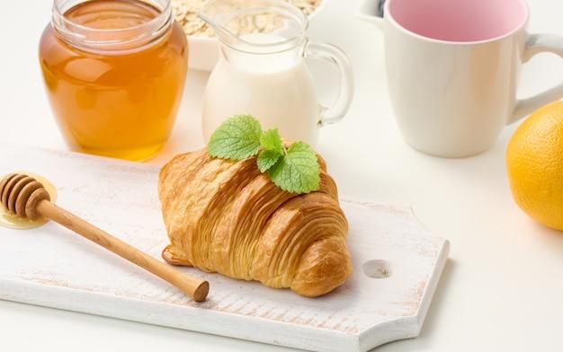 Pieczony świeży rogalik na desce, mleko i miód na białym stole. poranne śniadanie