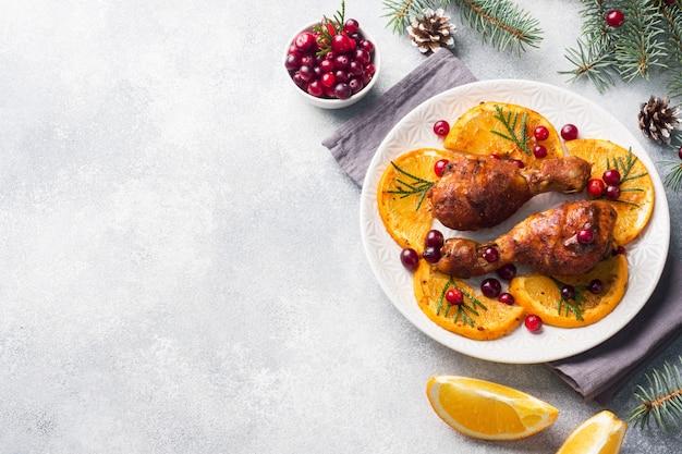 Pieczony udek z kurczaka z pomarańczami i żurawiną w talerzu jasnoszarym tle.