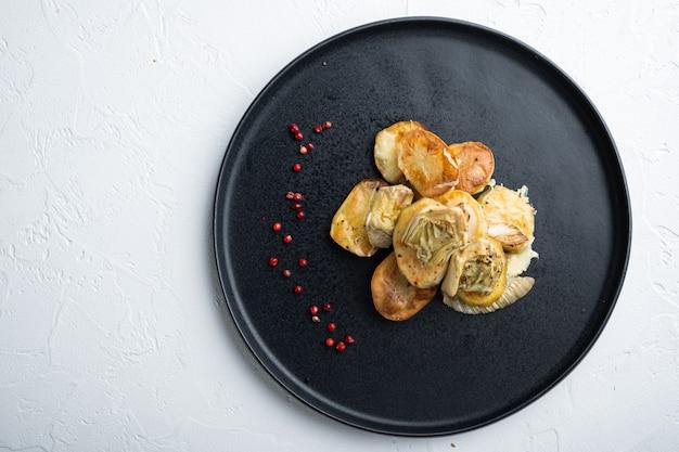 Pieczony ziemniak i karczoch z kopru włoskiego al forno, na białym tle z teksturą, widok z góry z miejscem na tekst