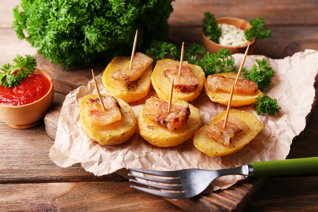 Pieczony ziemniak z boczkiem na drewnianej desce do krojenia, na drewnianym tle