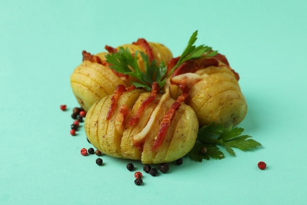 Pieczony ziemniak z boczkiem na miętowym tle.