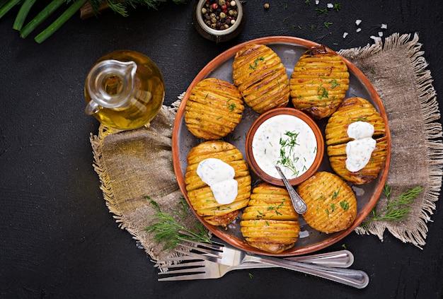 Pieczony ziemniak z ziołami i sosem. wegańskie jedzenie. zdrowy posiłek. widok z góry. leżał płasko