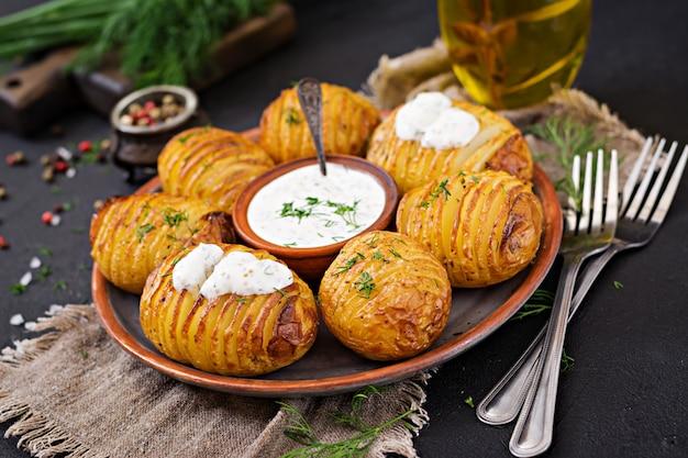 Pieczony ziemniak z ziołami i sosem. wegańskie jedzenie. zdrowy posiłek.