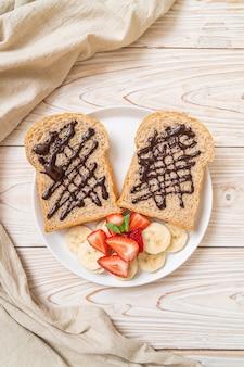 Pieczywo pełnoziarniste zapiekane ze świeżym bananem, truskawką i czekoladą na śniadanie