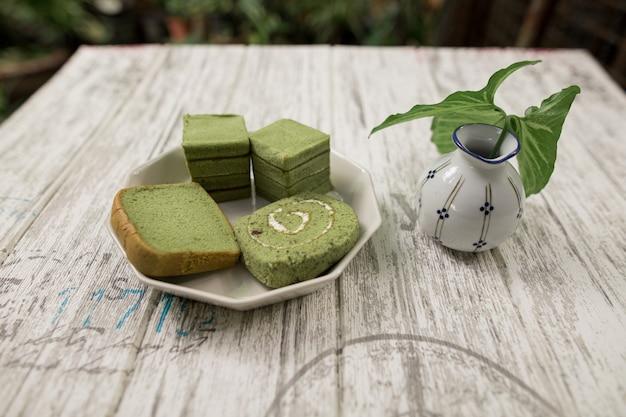 Pieczywo zielonej herbaty na białym talerzu i wazonie