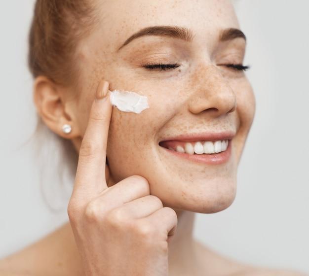 Piegowata imbirowa dama nakładająca na twarz krem przeciwstarzeniowy i uśmiech na białej ścianie studia