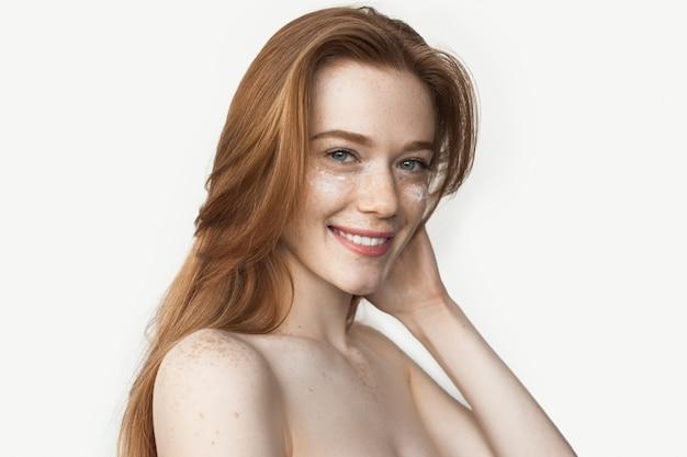 Piegowata kaukaska kobieta z rudymi włosami uśmiechająca się do kamery, pozująca z nagimi ramionami i kremem pod oczami