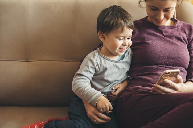 Piegowata kaukaska matka siedzi na sofie ze swoim małym chłopcem i używa telefonu komórkowego