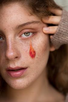 Piegowata kobieta z liśćmi na twarzy