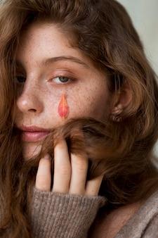 Piegowata kobieta z pomarańczowym liściem na twarzy
