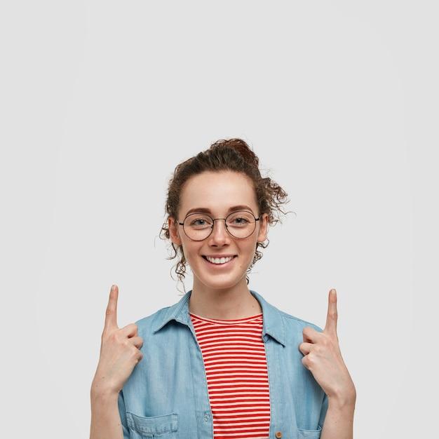 Piegowata nastolatka w okularach pozuje na białej ścianie