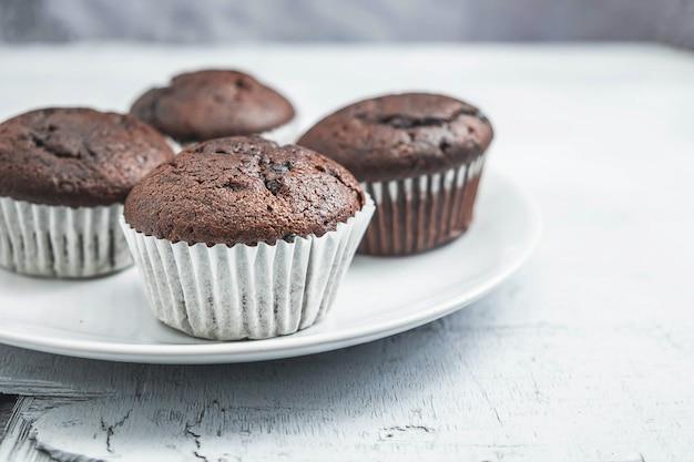 Piekarni czekoladowe babeczki w naczyniu na białym tle