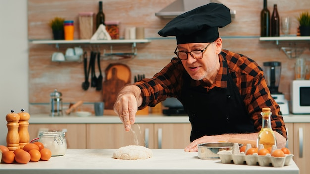 Piekarnia człowiek przesiewania mąki na ciasto na stole w domowej kuchni. emerytowany starszy kucharz z bonete i jednolitym kropiącym, przesiewającym, rozprowadzającym składniki rew z ręcznym pieczeniem domowej pizzy i chleba.