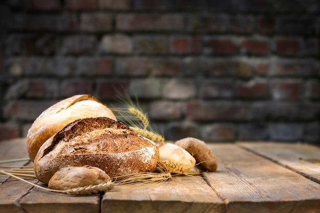 Piekarnia tło. zestaw świeżo upieczony chrupiący chleb i bułki z kłosami pszenicy na drewnianym stole w piekarni. przestrzeń ãƒâ ã,â¡opy