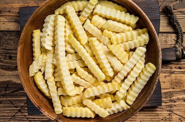 Piekarnik frozen crinkle frytki ziemniaczane patyczki w drewnianym talerzu