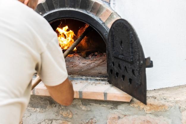Piekarnik zbudowany na zewnątrz i nierozpoznawalna osoba wkładająca drewno opałowe do środka