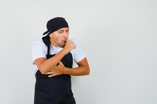 Piekarz cierpi na kaszel w koszulce, fartuchu i wygląda na chorego.