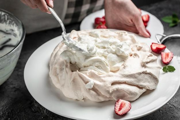 Piekarz dekorujący świeże pyszne domowe ciasto bezowe pavlova z bitą śmietaną i truskawkami