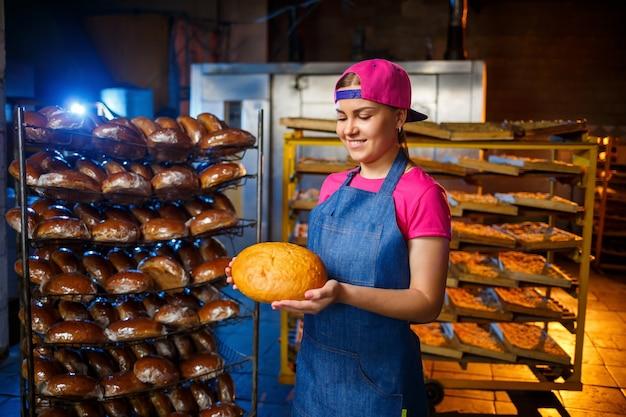Piekarz dziewczyna bierze gorący chleb w piekarni na tle regałów z chlebem. przemysłowa produkcja chleba. etap pieczenia w piekarni