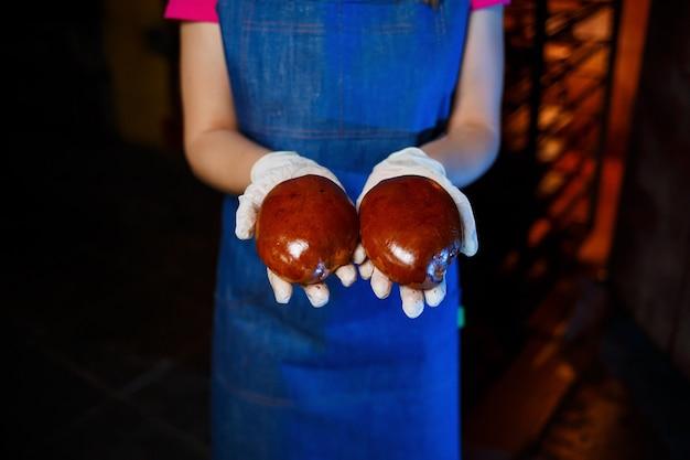Piekarz dziewczyna trzyma świeże ciasta w rękach piekarni. ma na sobie dżinsową sukienkę i czapkę. produkcja wyrobów piekarniczych. stojak z gorącymi chrupiącymi ciastami.