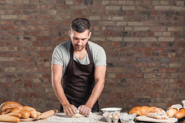 Piekarz jest ubranym fartucha ugniata ciasto na kuchennej kontuar pozyci przeciw ściana z cegieł