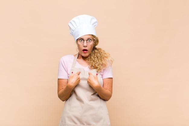 Piekarz kobieta w średnim wieku, wskazując na siebie