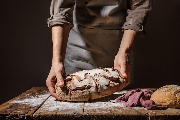Piekarz lub szef kuchni trzyma świeży chleb