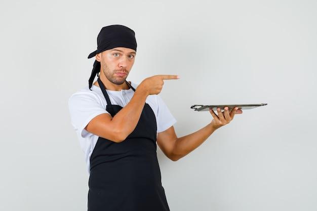 Piekarz mężczyzna trzyma metalową tacę