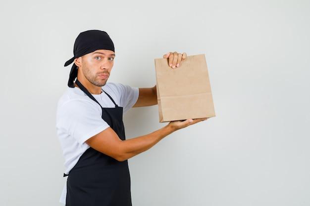 Piekarz mężczyzna trzyma papierową torbę w t-shirt