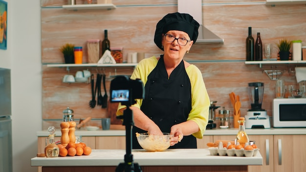 Piekarz noszący bonete nagrywa podcast z tradycyjnym przepisem na jedzenie z użyciem mąki i pękniętych jajek. szef kuchni influencer wykorzystujący komunikację internetową, strzelający w mediach społecznościowych za pomocą sprzętu cyfrowego
