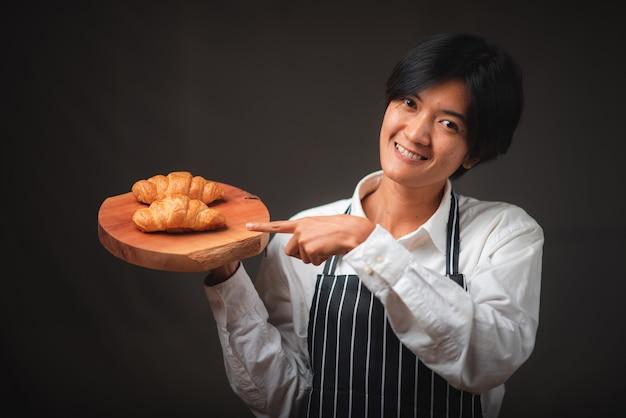 Piekarz prezentujący w kawiarni świeżo upieczone rogaliki z ciasta francuskiego wyglądające na pyszną, francuską koncepcję piekarni.
