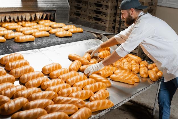 Piekarz toczy gorący świeży chleb, który opuścił przemysłowy piekarnik. automatyczna linia do robienia chleba