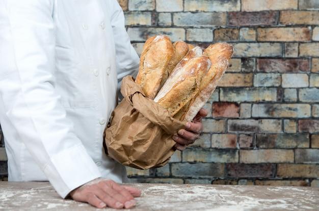 Piekarz trzyma tradycyjne chleb francuskie bagietki