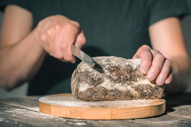 Piekarz trzymający w rękach świeży chleb